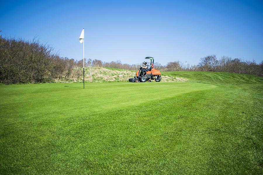Gustav klipper greenen på S:t Arild Golfklubb